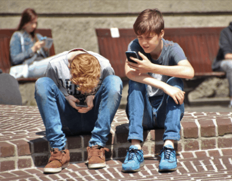 Two teenaged boys looking at their phones