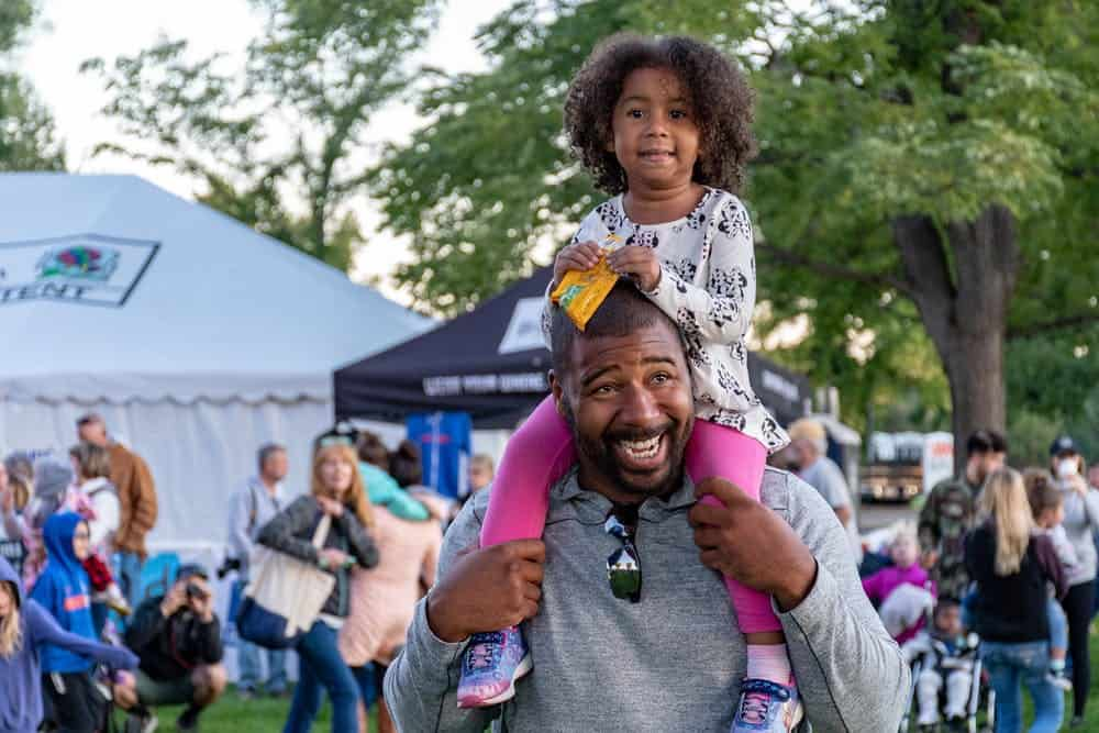 A Black dad smiling with his daughter on his shoulders