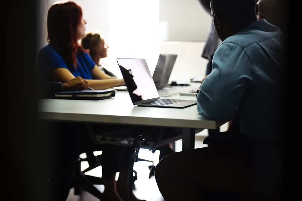 Several people in a meeting in an office with laptops open