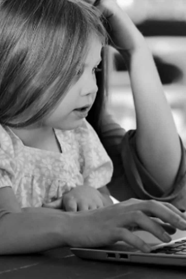 A young girl looking at a laptop screen with an adult