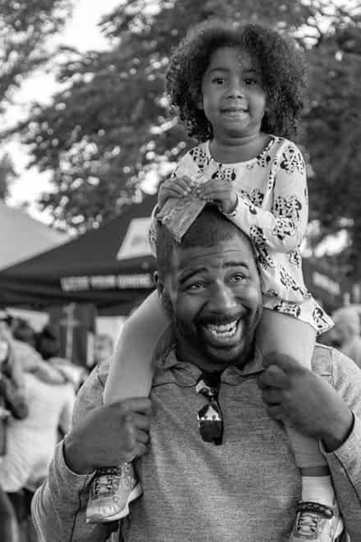 Black and white image of Black dad with his daughter on his shoulders